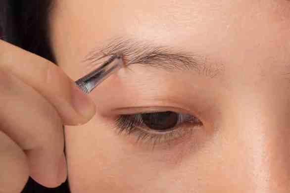 Image of woman plucking eyebrow with tweezer